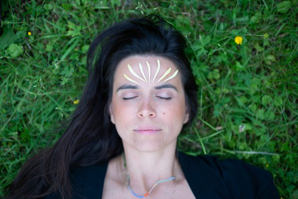 Isadora laying on the grass with flower petals in the head representing the mystical aspect of this New Moon in Pisces